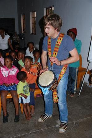 Max-Ole Tammen trommelt während eines Workshops in einem Township in Südafrika.