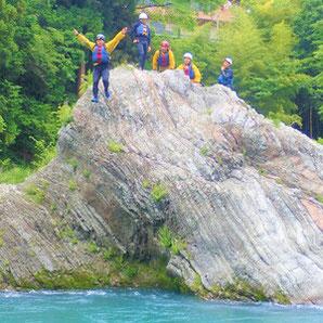 ラフティングツアーの途中岩から飛び込みをするゲスト