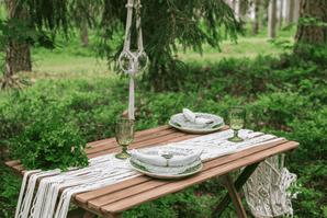 table bois dans la nature avec chemin de table macramé et couverts