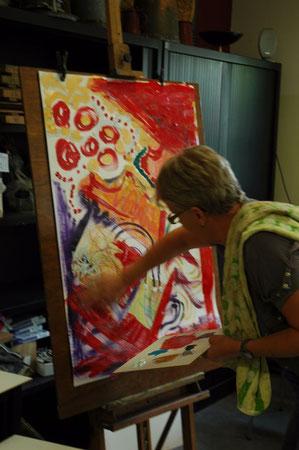 Cursist schildert in Atelier de Rode Draad met grote gebaren op haar schilderij van 1 bij 0,7 m, met geel, paars en nu veel rode acrylverf.