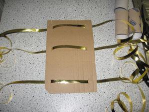 Sechs Ritzen für das Einfädeln der Bänder an zwei Seitenränder links und rechts der Pappe mit Messer einritzen.