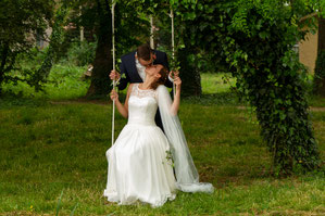 Junges Brautpaar küsst sich unter einem Baum auf einer Schaukel