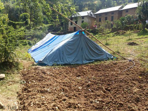 Zelte neben den beschädigten Häusern