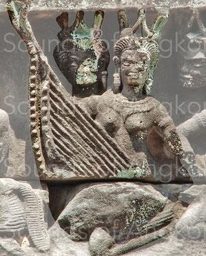 On voit ici deux harpes représentées l'une derrière l'autre. Celle à l'arrière présente 15 chevilles et certaines d'entre elles sont cassées. Banteay Samre.