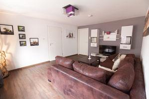 Wohnzimmer mit Couch, TV und Lampe