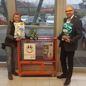 Mann und frau neben oranger Gitterbox für Futterspenden
