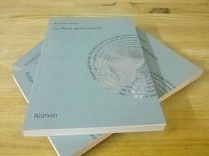 Auf dem Foto liegen drei Bücher übereinander auf einer Tischplatte. Immer das gleiche Buch. Zu Wort gekommen. Das Cover ist grau. Krisförmig sind Sätze angeordnet, die auf der rückseite des Covers zu finden sind. Darunter ist schwach ein Foto der Autorin.