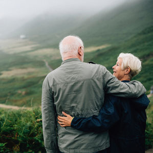 Old man and woman standing with arms wrapped around each other, looking over a green valley.