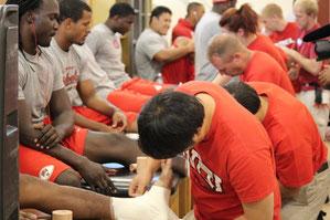 ネバダ大学フットボール部の選手にテーピングをする秋吉(手前)