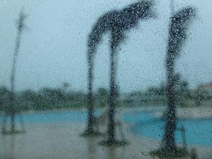 台風襲来中のプールサイドをガラス越しに屋内から撮影。ガラスに雨粒がびっしり.