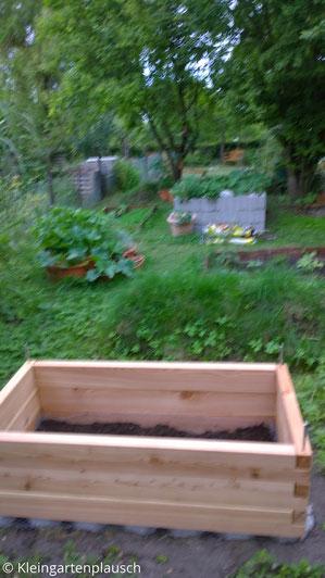 Im Vordergrund kleines Holzhochbeet, im Hintergrund Garten ...