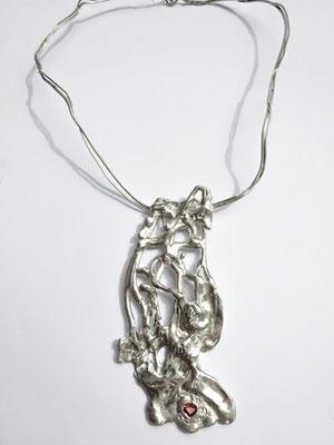 Un collier très irrégulier avec une pierre rouge vif est exposé sur fond blanc.