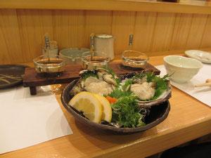 新鮮な岩牡蠣の刺身、奥は地酒の利き酒