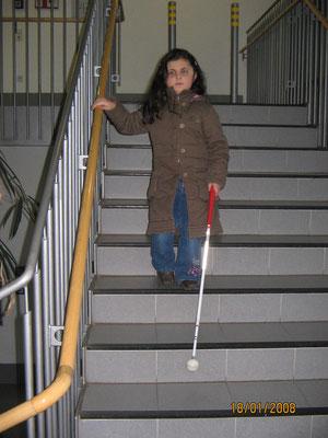 Schulkind beim Erlernen der Treppentechnik nach unten im Schulgebäude.