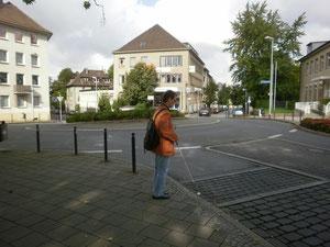 Überquerung am Kreisverkehr (li. Seite).  Der Langstock ertastet die Bordsteinkante.