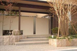 白いコンクリートの塀の向こうに中庭があります