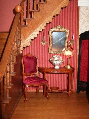 """Las escaleras las construyó Alfonso, incluso los barrotes. El centro de flores es de Reutter y el espejo es un marco de fotos pintado en dorado """"viejo"""". La tela de la pared es de un muestrario de tapicerías que me consiguió mi amiga Teresa."""