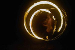 man sieht die Feuerspieler in der Mitte des Lichtballes