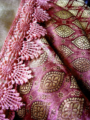 Close up of embroidered pewter design & pink lace border on grape-coloured section of silk brocade Indian throw