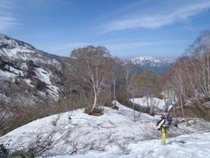 中飯場少し上をスキーを担いで、後ろは大長山