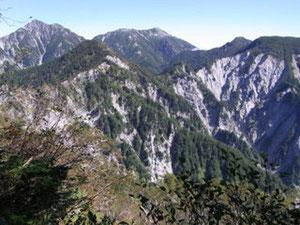 不動岳手前の稜線から、後ろは左から針ノ木岳、蓮華岳、北葛岳、手前に船窪岳第一ピーク(真ん中)、第二ピーク(左大きい)。基本的にあの崩壊した淵を回ります