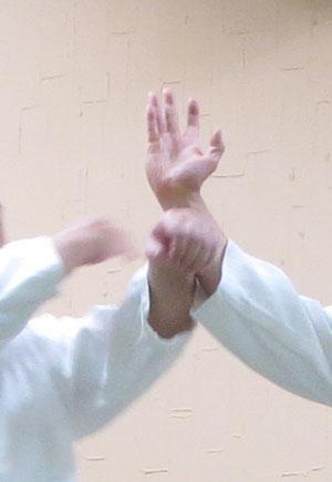 ②左足を外側に置き換え右魂氣を降氣の形で手刀の遠位に当てる