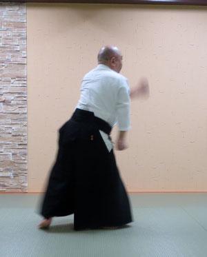 ⑤取りが右半身になると同時に左直突き 受けの右手は取りの右手と共に丹田に結び右半身から後方の足を前方に廻り込んで向き直って右半身(相半身)となる