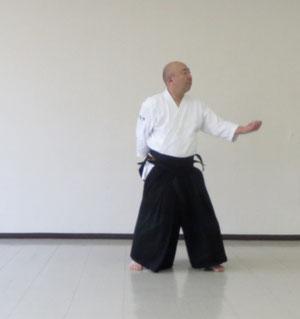 左足を一時軸として右足を内に回転して再び軸として左半身の陰の魄氣で後ろ回転 腰の後ろに結んだ受けは取りの目付と反対方向に体の変更
