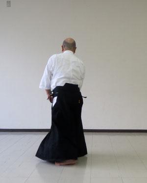 ⑤正面 前方の左足を後方に一歩置き換える 両手とも氣の巡りで陰の陰で丹田に結んでいる
