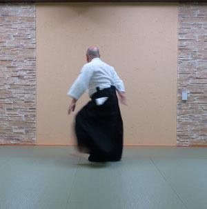 ④左足を一回転して後方へ置き換えて軸足とする その間腰の左手は左膝に膝の右手は腰に置き換える