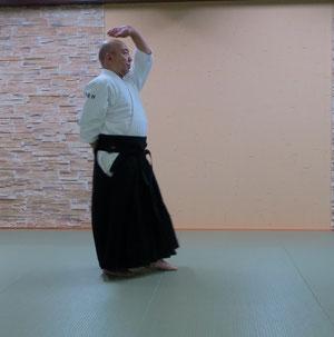 ③連続動作では後ろの左足で剣線を渡って左半身で振りかぶる 陽の魄氣のときは手刀で頭上に挙げる