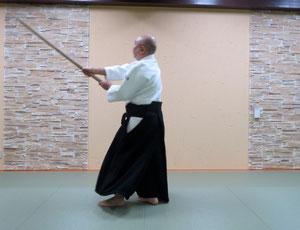 ③右足を軸として後方の足も剣線を跨いで一歩前方に置き換え右手は回外して真中を打つと左半身