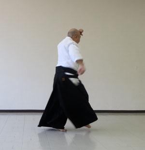 ④右足を後方から前方を経て膝を折って軸足の外側に着地 右手は腰の後ろに置く 額の結びを緩めると回転は不能