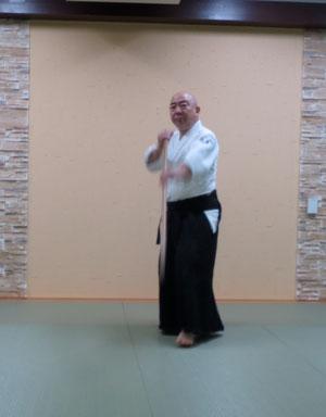 右足を踏み替えて軸とし左足を半歩前に置き換え左半身入り身で振り込み突き