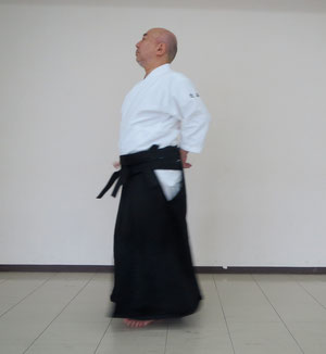 片手取り呼吸法裏 ⑦左足を送り足 右手は体側に巡って残心  相対動作では受けが取りの真後ろに沿って地に結ぶ