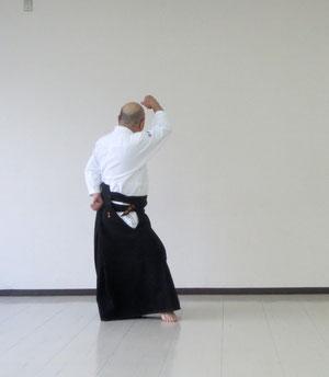 ②左足を軸とし右足で剣線を外して陰の魄氣 右手を降氣の形で額に結んで受け流し