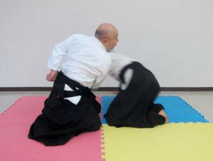 ⑦受けの左手は 地に結んでいる右手と左膝を結ぶ線を底辺とする三角形の頂点(丹田の直下)に結ぶ 入り身運動の姿勢・目付を維持して丹田を受けから離さない