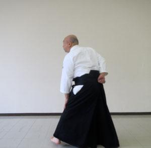 ②左足先を剣線に直角で内方向に踏み替えて軸とし 左手を膝に右手を腰に置く