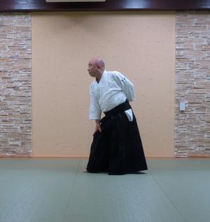 ②右足を軸として足先を剣線に直角とする 右手を右膝に左手は腰に置く 同時に目付を軸足先方向へ