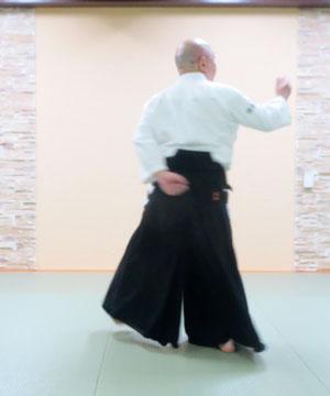 ④右足を軸として左足を180度余り内側に回転して次の軸足に 膝上の左手を陰の陽で腰に右手は腰から陽の陽 目付を右手掌に