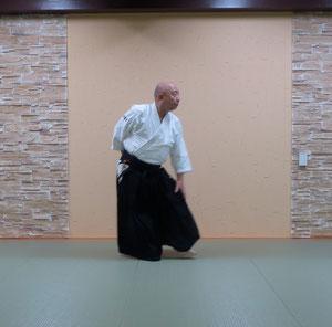 ②左足を軸として足先を剣線に対して左外へ直角に向ける 膝に手を置き右手は腰へ 目付を軸足先方向へ