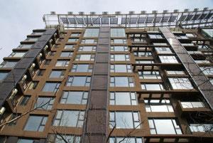 温水タンクは、水平な真空チューブと共にバルコニーの外へ設置(写真左の方、壁の後ろ)。チューブは各タンクの上部に接続され、建物20階分のタンク全てをつないでいる。