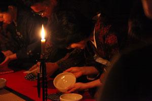 和ろうそくの明かりの下、本田さんの作品を拝見する参加者たち