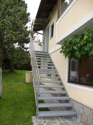 Stahltreppe mit Edelstahlgeländer und Edelstahl- Glas Windfang