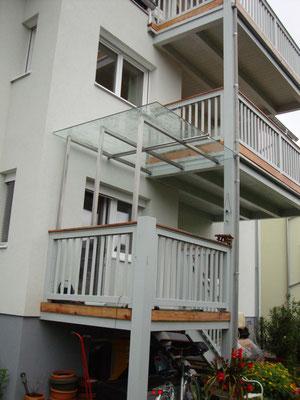 Vordach aus Edelstahlkonstruktion mit VSG- Glaseindeckung