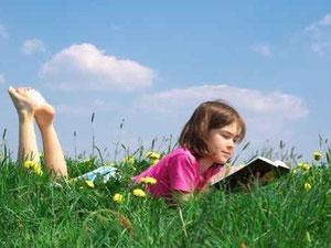 Mädchen liest Buch auf Wiese