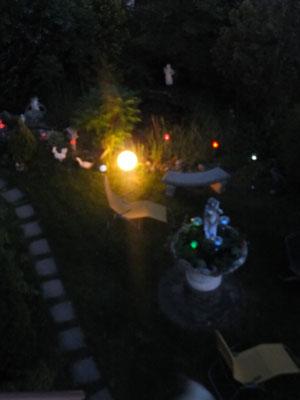 Blick von Balkon auf unseren bunt beleuchteten Garten am Abend.