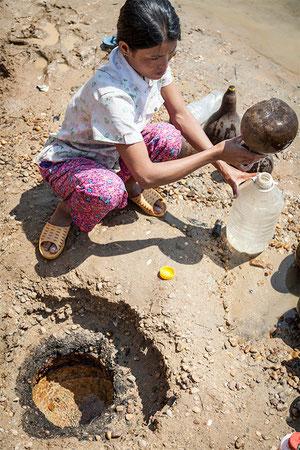Recogiendo agua del río para consumo