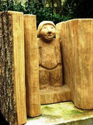 Holzfigur im Säulen-Rahmen.