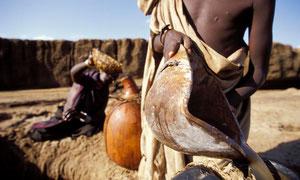 Ragazze Turkana prendono acqua in un pozzo scavato nel letto di un fiume secco